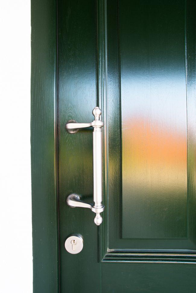Grüne Holztür mit Edelstahlgriff